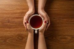Kvinna och man som rymmer den varma kopp te på trätabellen royaltyfri bild