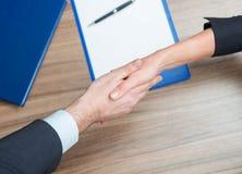 Kvinna och man som skakar händer över papper och penna på tabellen Fotografering för Bildbyråer