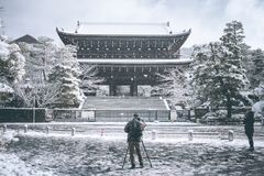 Kvinna och man som tar foto den japanska templet med hennes smartphone och hans digitala kamera Arkivbild