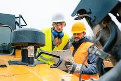 Kvinna- och manarbetare i villebråd på utgrävningmaskinen arkivfoton
