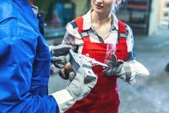 Kvinna- och manarbetare som kontrollerar m?tningar av metallarbetsstycket royaltyfri bild
