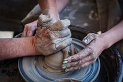 Kvinna- och manhänder Pilla på arbete Skapa disk Hjul för keramiker` s Smutsiga händer i leran och keramiker`en s rullar Royaltyfri Fotografi