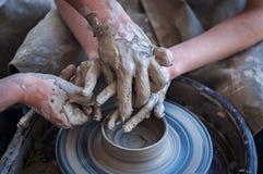Kvinna- och manhänder Pilla på arbete Skapa disk Hjul för keramiker` s Smutsiga händer i leran och keramiker`en s rullar Royaltyfri Foto