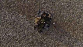 Kvinna- och mansammanträde på filten på stranden som ser upp och vinkar, flyg- sikt stock video