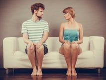 Kvinna- och mansammanträde på soffan som till varandra ser Fotografering för Bildbyråer