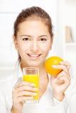 Kvinna och ny orange fruktsaft Arkivfoto