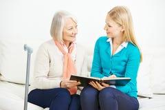 Kvinna och pensionärkvinna med fotoalbumet Royaltyfri Fotografi