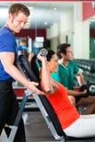 Kvinna och personlig instruktör i idrottshall, med hantlar Royaltyfri Fotografi