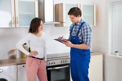 Kvinna och Repairman In Kitchen fotografering för bildbyråer