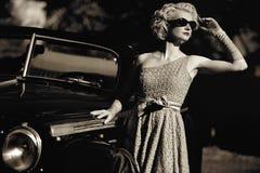 Kvinna och retro cabriolet Arkivfoton