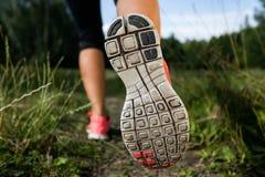 Kvinna och running skor i skogen som övar Arkivfoto