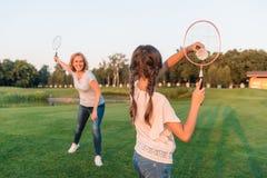 Kvinna och sondotter som spelar badminton Arkivbild