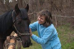 Kvinna och svart häst Royaltyfri Bild