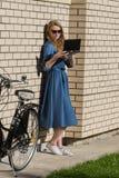 Kvinna- och tappningcykel- och vittegelstenvägg, grön gräsmatta Den blonda flickan står utanför ett kontor som rymmer en minnesta Arkivfoto