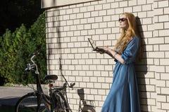 Kvinna- och tappningcykel- och vittegelstenvägg, grön gräsmatta Den blonda flickan står utanför ett kontor som rymmer en minnesta Royaltyfri Bild