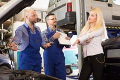 Kvinna och två auto mekaniker Arkivfoton