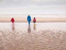 Kvinna och två småbarn på vinterstranden Royaltyfri Fotografi