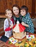 Kvinna och ungar som förbereder ett fågelhus i höst Royaltyfri Foto