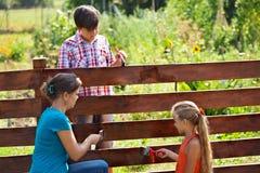 Kvinna och ungar som målar det trädgårds- staketet Royaltyfria Bilder