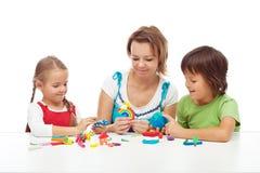 Kvinna och ungar som spelar med färgrik lera Arkivfoto
