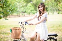 Kvinna på att le för cykel Arkivfoto