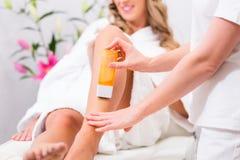 Kvinna på att vaxa hårborttagning i skönhetmottagningsrum arkivfoton