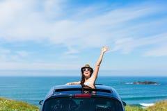 Kvinna på att vinka för bilsemesterlopp Royaltyfri Foto