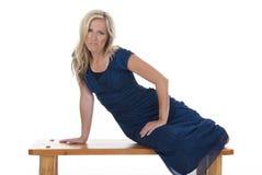 Kvinna på bänk i blåttklänning Fotografering för Bildbyråer