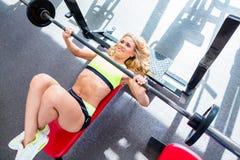 Kvinna på bänkpress, i att öva för idrottshall Royaltyfri Foto