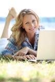 Kvinna på bärbar dator utanför Royaltyfria Bilder