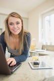 Kvinna på bärbara datorn med den smarta telefonen och minnestavlan Arkivfoton
