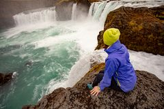 Kvinna på bakgrunden av en vattenfall iceland arkivbilder