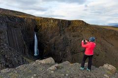Kvinna på bakgrunden av en vattenfall iceland arkivfoton