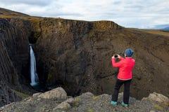 Kvinna på bakgrunden av en vattenfall iceland arkivbild