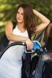 Kvinna på bensinstationen som tankar hennes bil Fotografering för Bildbyråer
