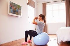 Kvinna på boll som utarbetar till kondition DVD på TV i sovrum fotografering för bildbyråer