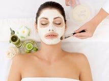Kvinna på brunnsortsalongen med den kosmetiska maskeringen på framsida Royaltyfria Bilder