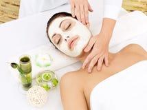 Kvinna på brunnsortsalongen med den kosmetiska maskeringen på framsida Royaltyfri Foto