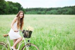 Kvinna på cykeln i fält royaltyfri fotografi