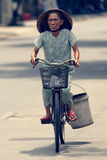 Kvinna på cykeln i Hoi An royaltyfri foto