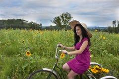 Kvinna på cykeln med solrosor Fotografering för Bildbyråer