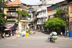Kvinna på cykeln som transporterar gods i Hanoi, Vietnam Royaltyfria Bilder