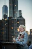 Kvinna på den Brooklyn bron som ser Manhattan med ett kaffe arkivfoton