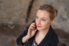 Kvinna på den gamla byggnaden som talar på telefonen Royaltyfri Bild
