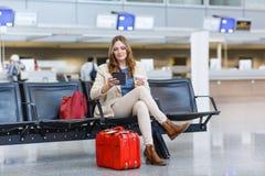 Kvinna på den internationella flygplatsen, läs- ebook och drickacoffe Royaltyfria Bilder