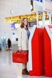 Kvinna på den internationella flygplatsen som kontrollerar in på elektronisk termin Royaltyfria Foton