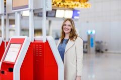 Kvinna på den internationella flygplatsen som kontrollerar in på elektronisk termin Arkivfoton