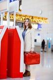 Kvinna på den internationella flygplatsen som kontrollerar in på elektronisk termin Royaltyfri Fotografi