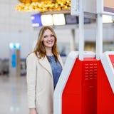 Kvinna på den internationella flygplatsen som kontrollerar in på elektronisk termin Royaltyfri Foto