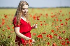 Kvinna på den röda klänningen med den scharlakansröda vallmo Arkivfoto